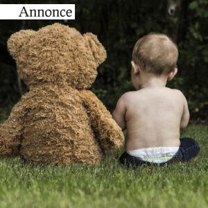 En baby med sin bamse siddende i naturen.